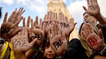 """zzzzinte1Supporters of Colombian president and presidential candidate Juan Manuel Santos raise their hands with the word """"Peace"""" written on them during a peace event in Bogota, on June 11, 2014. Colombia's government and the country's second largest guerrilla group, the National Liberation Army (ELN), announced on the eve they have opened peace talks, which adds to those taking place with the FARC, with a tense runoff presidential election just days away. AFP PHOTO/Diana Sanchez zzzz"""
